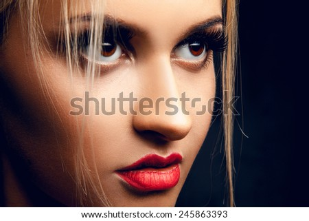 Close up portrait of gorgeous blonde girl looking away. Brown eyes. Professional make up. Studio shot - stock photo