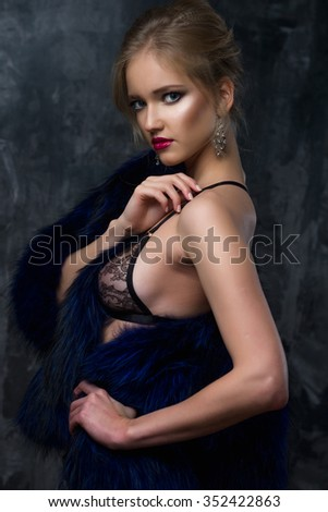 Close-up portrait of gorgeous blonde young woman in celebrity style with perfect make up and hair style wearing sexy lingerie and blue fur. Fashion beauty photo, dramatic look - stock photo
