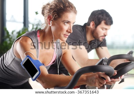 Close-up portrait of gym members participating in a spinning class while training together at fitness center. Sporty woman listening music at her mobile phone.  - stock photo