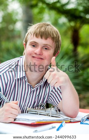 Close up portrait of handicapped student doing thumbs up at desk outdoors. - stock photo