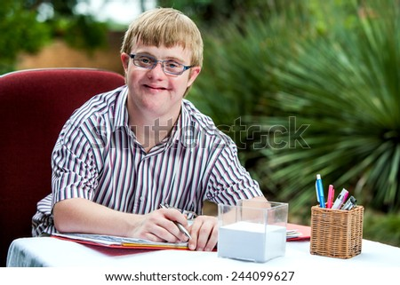 Close up portrait of handicapped student wearing glasses at desk in garden. - stock photo