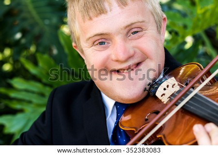 Close up portrait of handicapped violinist playing violin against green background. - stock photo
