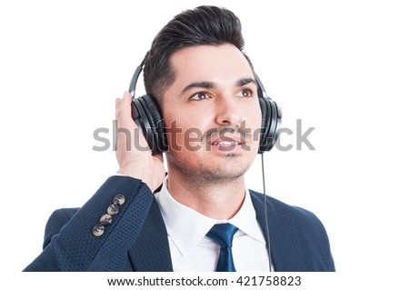 Close-up portrait of handsome businessman with headphones listening to music and looking up  isolated on white - stock photo