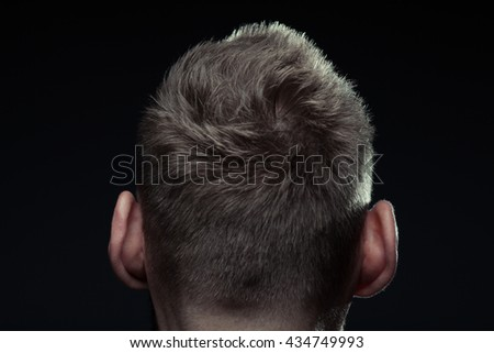 Close up portrait of handsome charismatic man's back posing over dark gray background. Modern stylish haircut. Studio shot - stock photo
