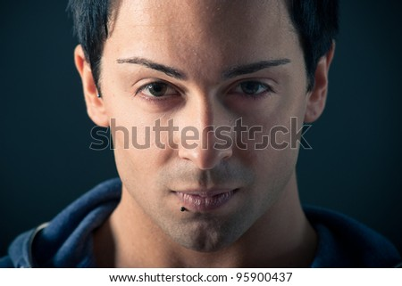 Close up portrait of handsome, confident man on dark background. - stock photo
