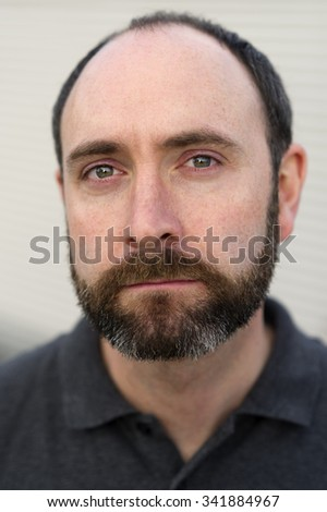 Close up portrait of handsome man with neatly trimmed beard. This is a photo taken with a shallow depth of field and using natural light. - stock photo