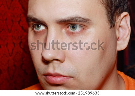 Close up portrait of handsome serious man in orange t-shirt indoor - stock photo