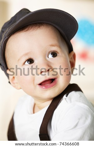 Close up portrait of handsome smiling caucasian baby boy with grey cap sitting and looking up. - stock photo