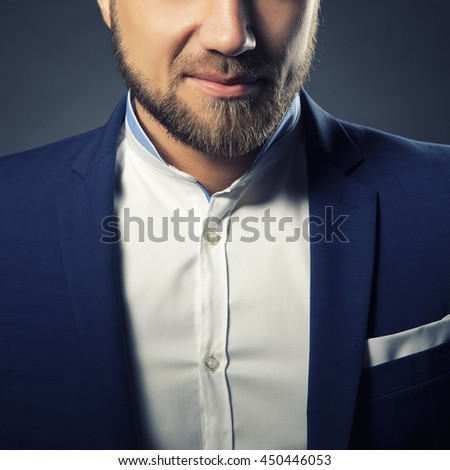 Close-up portrait of handsome stylish caucasian bearded young man in elegant blue suit and white shirt with perfect hair style smiling when looking at camera. Toned - stock photo