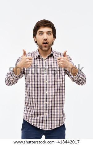 Close-up portrait of handsome surprised young blue-eyed dark-haired man wearing casual plaid shirt and jeans looking at camera showing thumbs up. Isolated on white background. - stock photo