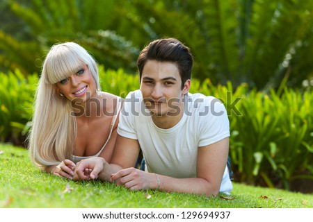 Close up portrait of handsome young couple laying on green grass in park. - stock photo
