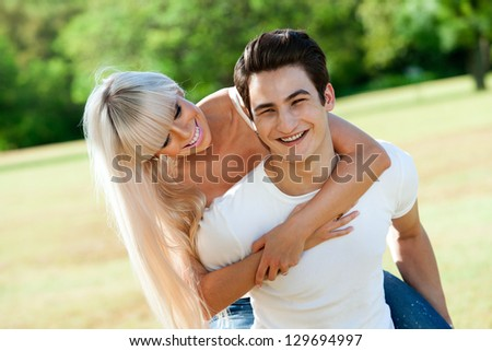 Close up portrait of handsome young couple piggybacking in sunny park. - stock photo