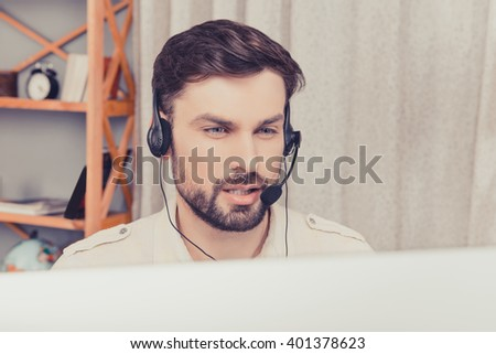 Close up portrait of handsome young worker in head-phones - stock photo
