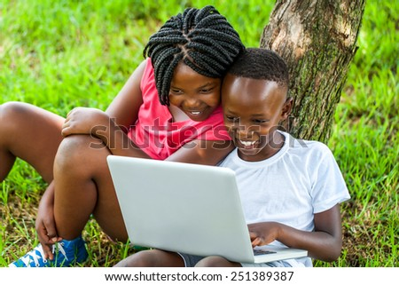 Close up portrait of happy African boy and girl playing on laptop under tree. - stock photo