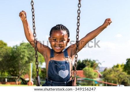 Close up portrait of Happy African kid raising arms on swing in park. - stock photo