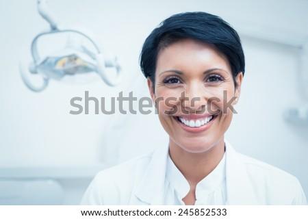Close up portrait of happy confident female dentist - stock photo