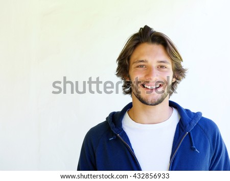 Close up portrait of happy handsome young man against white background - stock photo