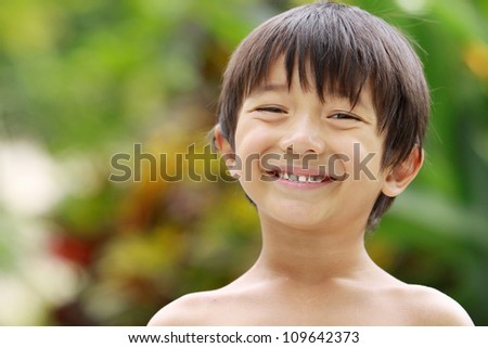 close up Portrait of happy joyful little boy smiling in summer day at the park - stock photo