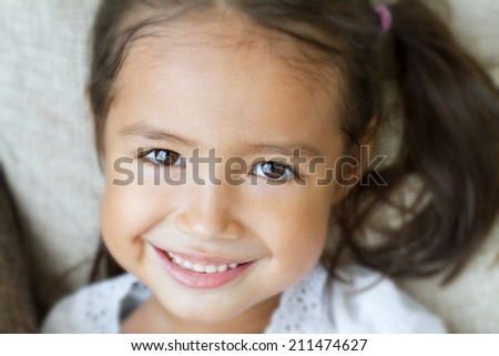 close-up portrait of happy, positive, smiling, playful asian caucasian girl - stock photo
