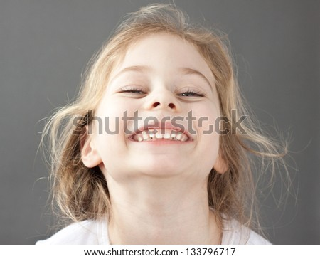 Close up portrait of happy smiling caucasian five years old blond child girl on a grey background - stock photo