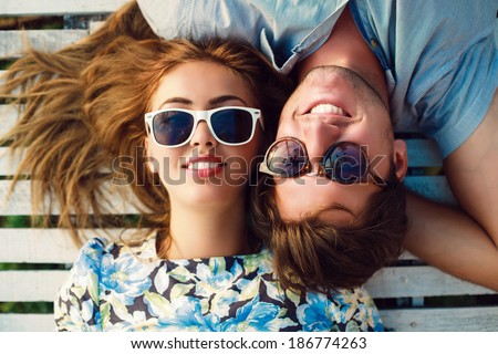 Close up portrait of happy smiling couple in love laying in wood white floor. Wearing retro clothes and sunglasses. Reflection of palm trees in glasses. - stock photo