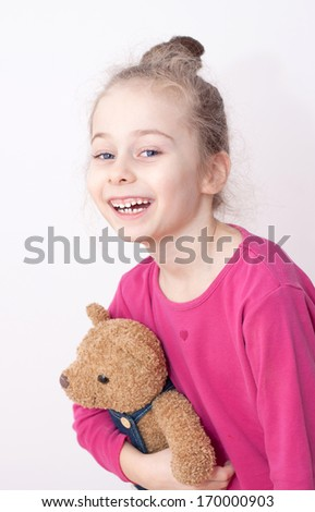 Close up portrait of happy smiling five years old caucasian blond child girl in pyjamas holding teddy bear on a white background. Bedtime - careless childhood. - stock photo