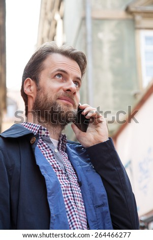 Close up portrait of happy smiling forty years old caucasian man in casual clothes talking on a mobile phone. City buildings as background. - stock photo