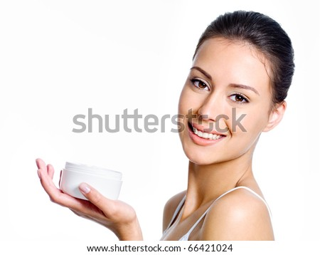 Close-up portrait of happy young beautiful woman holding moisturizing facial cream - isolated on white - stock photo