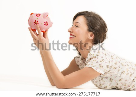 Close up portrait of happy young beautiful woman laying down holding in hands pink piggy bank, studio shot on white background - stock photo