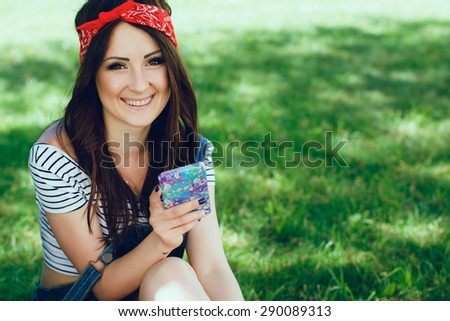 Close-up portrait of happy young brunette girl, sitting on the grass with mobile phone. Wearing red bandana and striped top. Summer day. Copy space. - stock photo