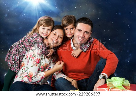 Close up portrait of happy young couple with their two kids next to Christmas gift. - stock photo