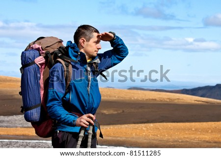 close up portrait of hiker looking at the horizon in the mountains on sunny day - stock photo