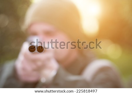 Close up portrait of hunter with his rifle in spring forest, hunter holding a rifle and waiting for prey, hunter shooting  - stock photo