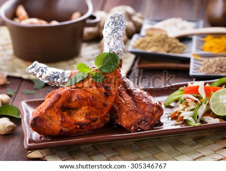 close up portrait of indian tandoori chicken garnished - stock photo