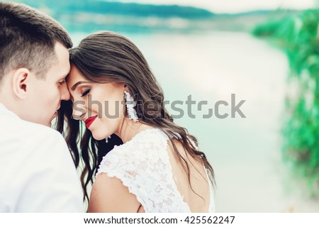 Close up portrait of kissing couple against river and green trees in the park. Beautiful young woman with long dark wavy hair kissing handsome man outdoors. Cute newlyweds on their wedding ceremony. - stock photo