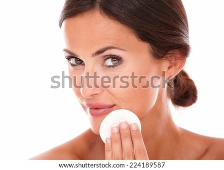 Close up portrait of latin woman applying moisturizer on her face while looking at camera on isolated studio - stock photo