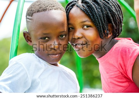Close up portrait of little African brother and sister joining heads outdoors in park. - stock photo