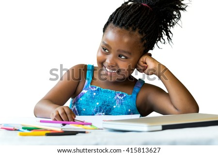 Close up portrait of little african girl at desk with color pencils and laptop.Isolated on white background. - stock photo