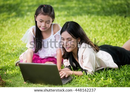 Close up portrait of little asian girl with braids and mother with laptop. Kid typing on laptop against green background outdoors. - stock photo