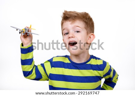 Close up portrait of little boy playing with an airplane toy - stock photo