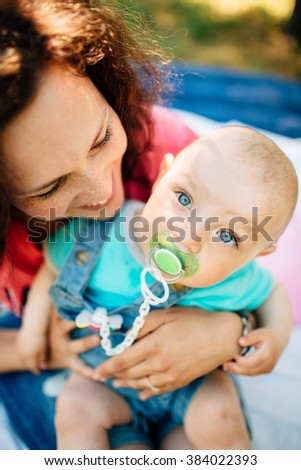 Close up portrait of little boy with big blue eyes and his young happy mother in park - stock photo