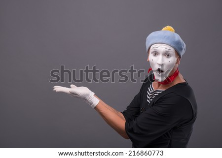 Close-up portrait of male mime with grey hat and white face funny smiling to the camera and panhandling isolated on grey background with copy place - stock photo