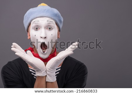 Close-up portrait of male mime with grey hat surprised opening his mouth and holding his hands near his face and looking at the camera isolated on grey background with copy place - stock photo
