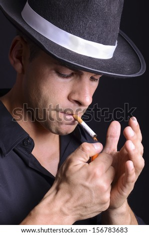 Close up portrait of man smoking cigarette on dark background - stock photo