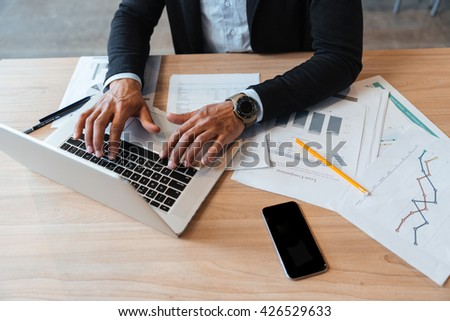 Close-up portrait of mans hands typing on the laptop in the office  - stock photo