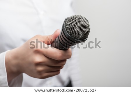 Close up portrait of microphone, which is hold by woman tv reporter and visible on the foreground.  - stock photo