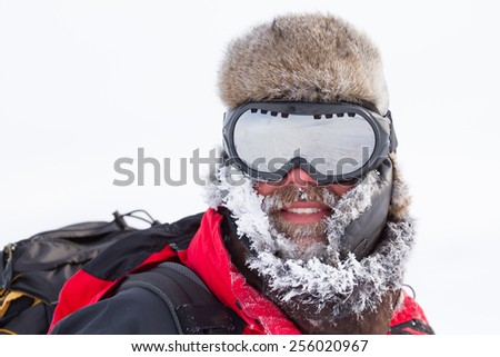 close-up portrait of middle aged men adventurer with frosted beard goggles and fur-cap during winter expedition - stock photo