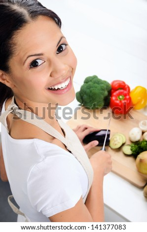 Close up portrait of mix race woman cooking and preparing food in the kitchen - stock photo