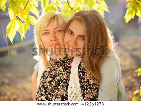 Close up portrait of mother and daughter hugging. Beautiful mother and her adult daughter. - stock photo