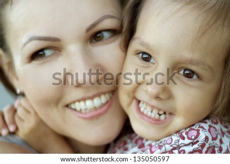 close-up portrait of mother and daughter on the walk in the summer - stock photo